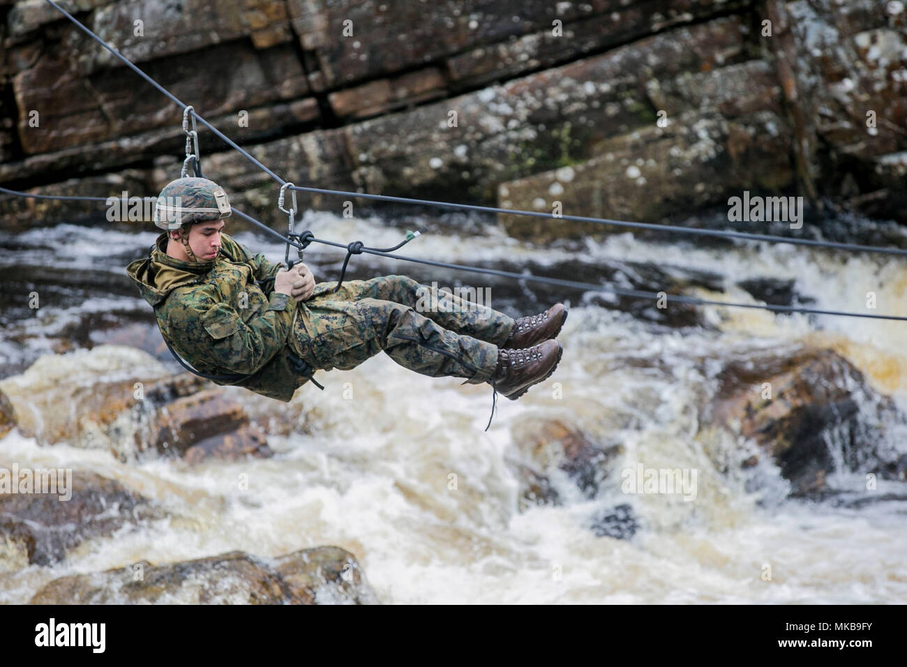 U.S. Marine with Marine Rotational Force Europe (MRF-E) crosses a river using a zip-line during exercise Green Claymore in Strathgarve, Scotland, Nov. 26, 2017. Green Claymore is a pre-Arctic training course lead by the British Royal Marines, designed to improve mountaineering and cold-weather survival skills. (U.S. Marine Corps photo by Cpl. Careaf L. Henson/Released) - Stock Image