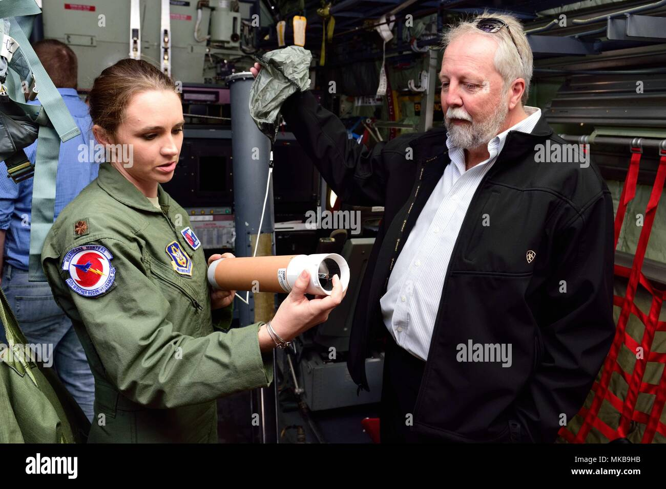 """Maj. Ashley Lundry, 53rd Weather Reconnaissance Squadron aerial reconnaissance weather officer and chief scientific officer, shows a weather data-gathering instrument called a dropsonde to Dr. Fred """"Marty"""" Ralph, Researcher and Director for the Center of Western Weather and Water Extremes, Scripps Institute of Oceanography, Nov. 29, 2017, at Brown Field Airport, San Diego, California. Hurricane Hunters met with Ralph and other Scripps scientists that day to discuss plans for participating in atmospheric river reconnaissance missions in early 2018. (U.S. Air Force photo by Tech. Sgt. Ryan Labad - Stock Image"""