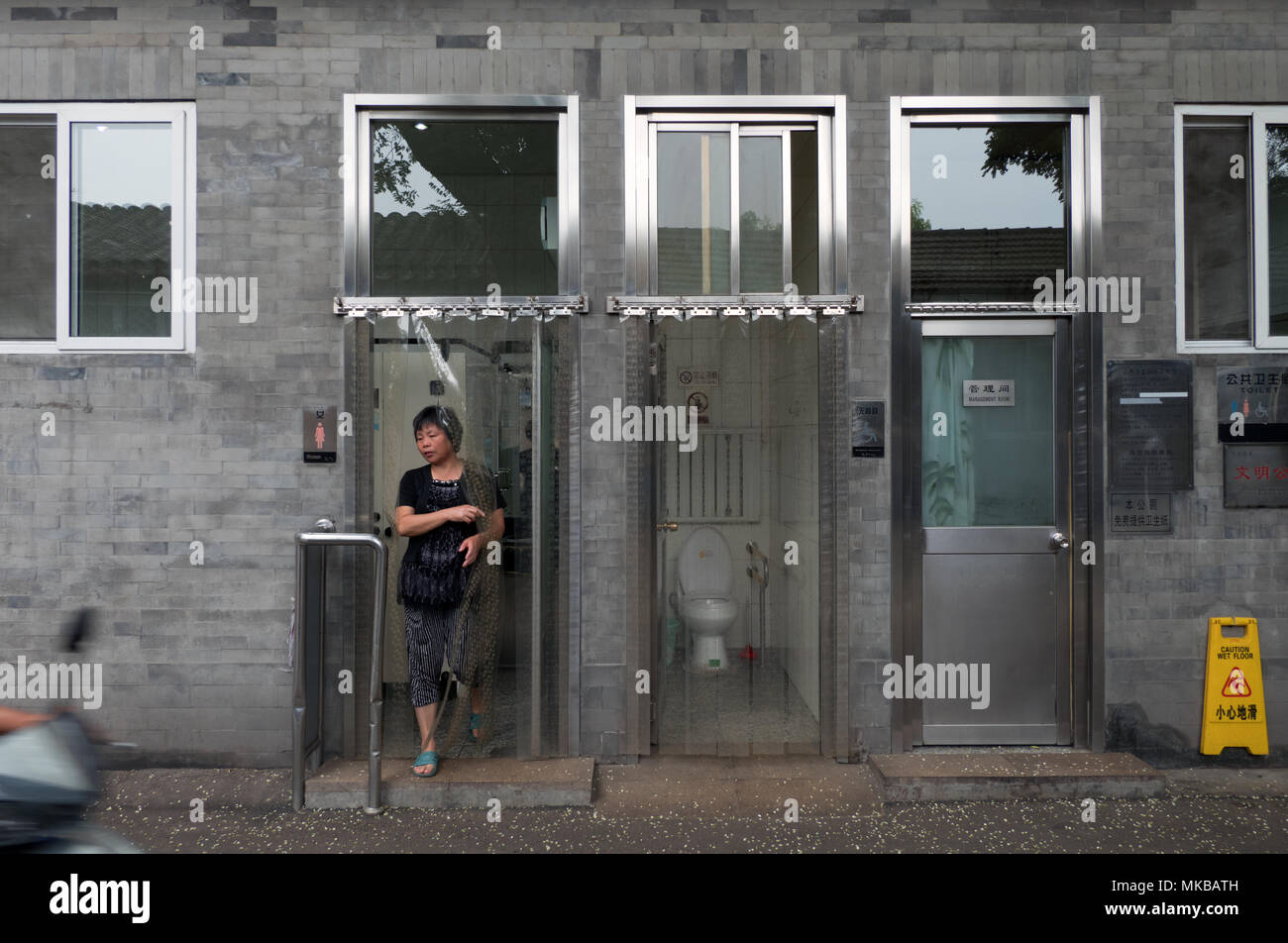 Daily life in a hutong (traditional old narrow street) of Beijing, China, Asia. Woman in public restrooms - Stock Image