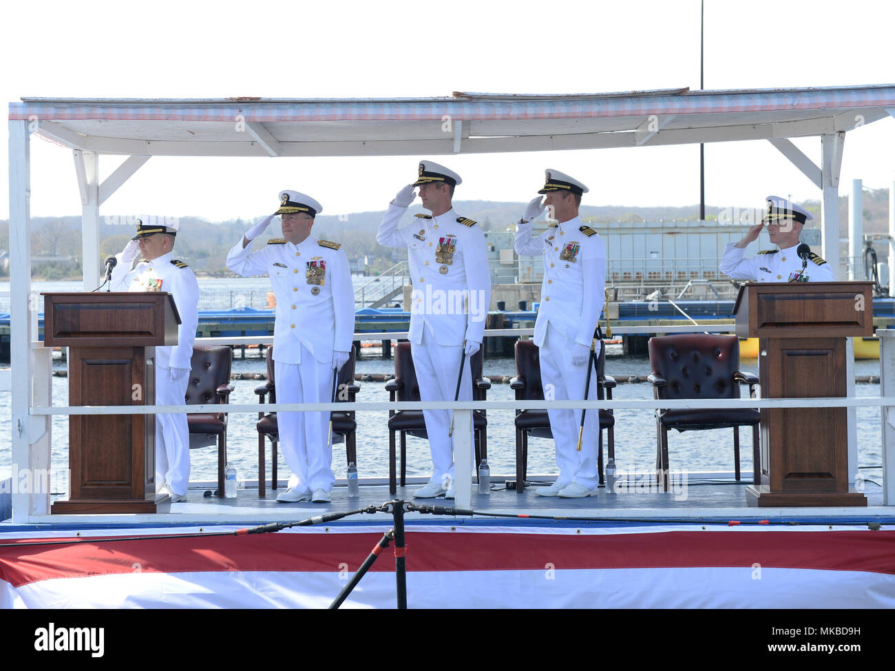 180503-N-LW591-020 GROTON, Conn. (May. 3, 2018) The official party salutes the colors during the change of command ceremony for Commander, Submarine Squadron (COMSUBRON) 12 onboard the Los Angeles-class, nuclear-powered, fast-attack submarine USS San Juan (SSN-751) at Naval Submarine Base New London in Groton, Conn., Thursday, May 3. Capt. David Youtt relieved Capt. Ollie Lewis as the commander of COMSUBRON 12. The mission of COMSUBRON 12 is to provide attack submarines that are ready, willing, and able to meet the unique challenges of undersea combat and deployed operations in the unforgiving - Stock Image