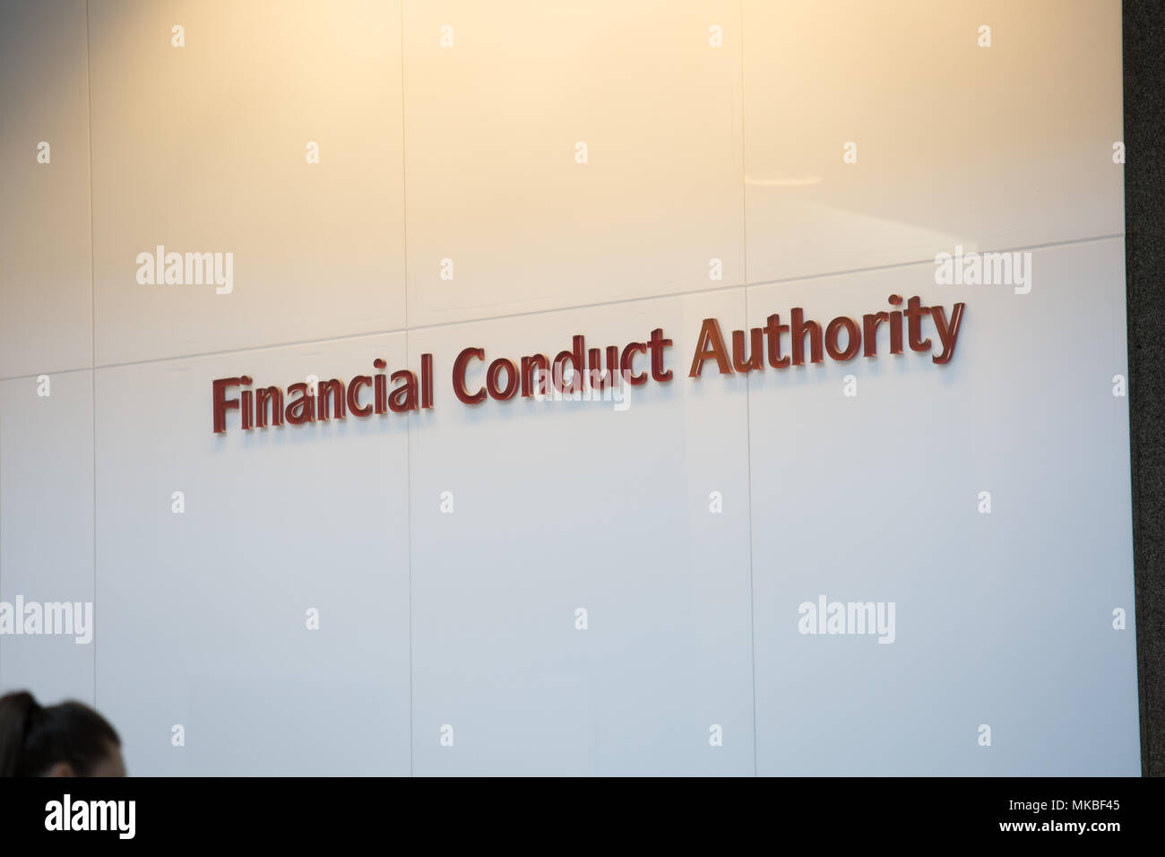 Financial Conduct Authority (FCA) offices, North Colonnade, Docklands, London. Reception showing corporate logo with employees entering through securi - Stock Image