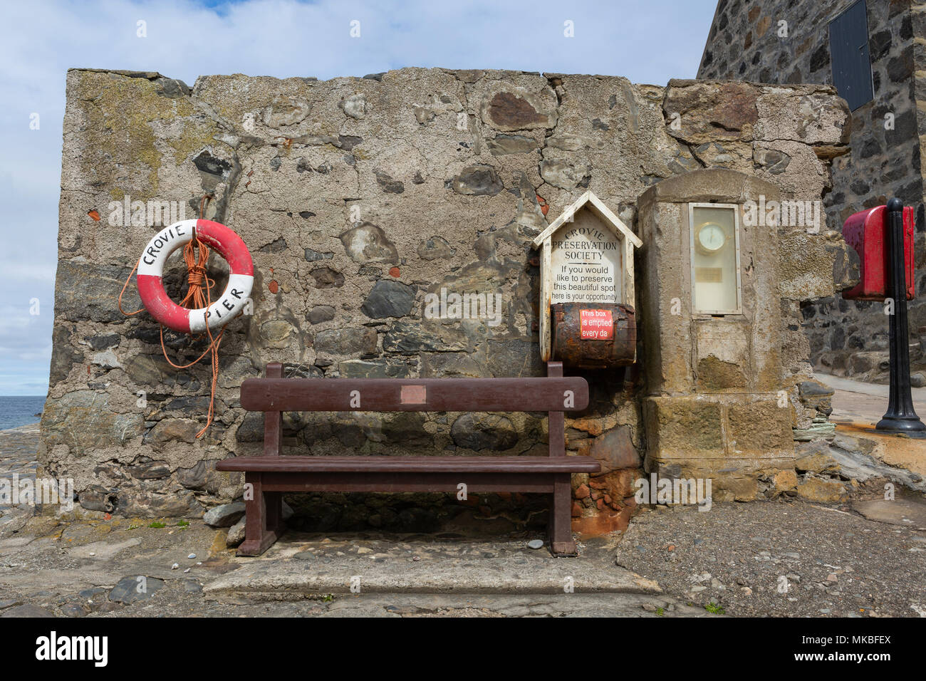 Seat, lifebelt, barometer and donation box at the pier, Crovie, Aberdeenshire, Scotland, UK - Stock Image