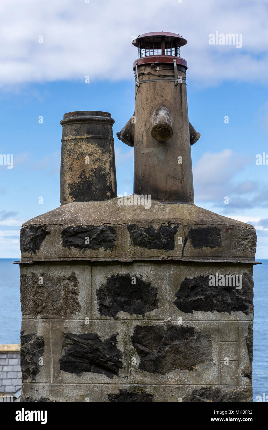 Chimney pots and stack on a cottage in the fishing village of Crovie, Aberdeenshire, Scotland, UK - Stock Image