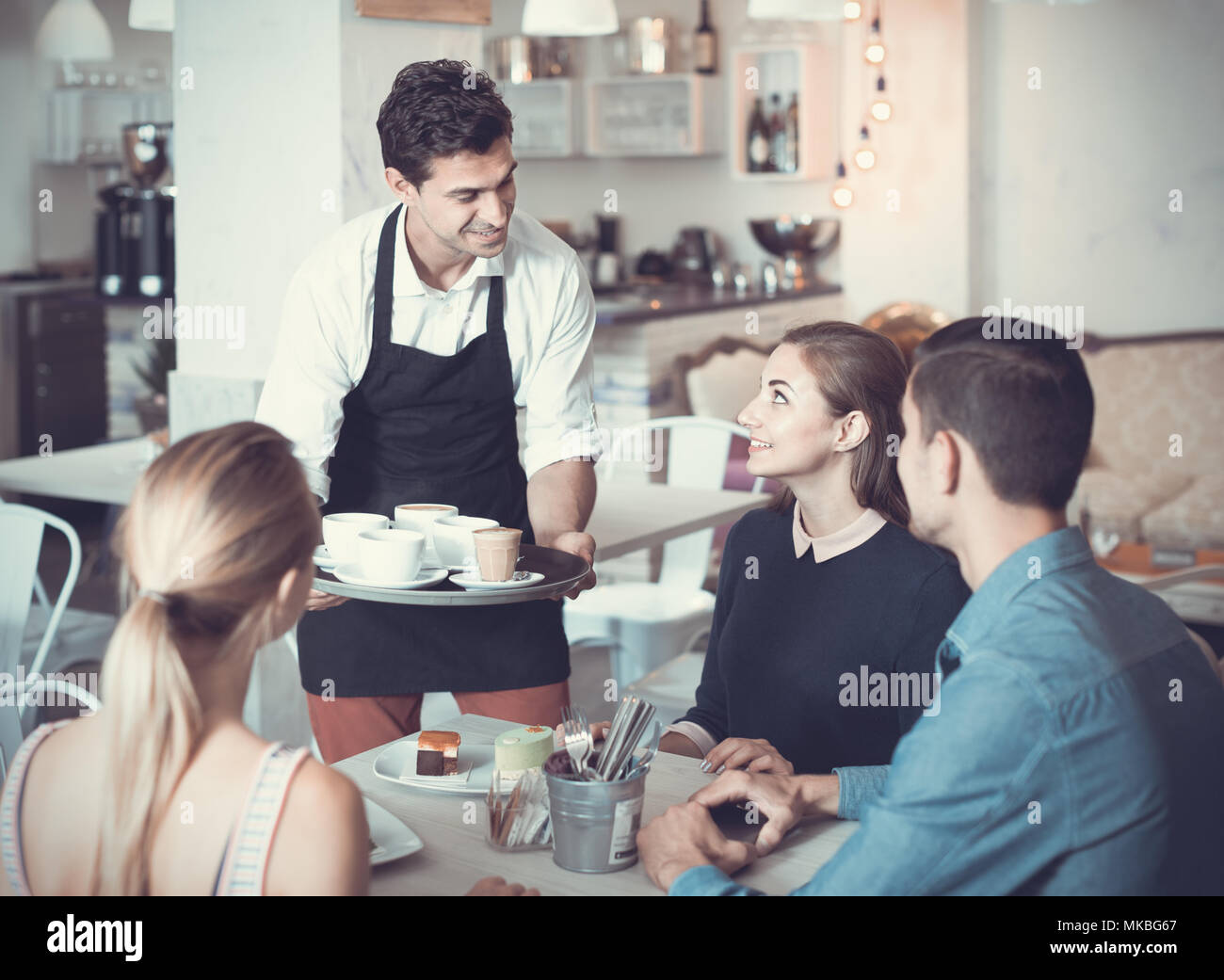 Polite smiling waiter bringing ordered dishes to friends in tearoom of a cozy confectioner's shop - Stock Image