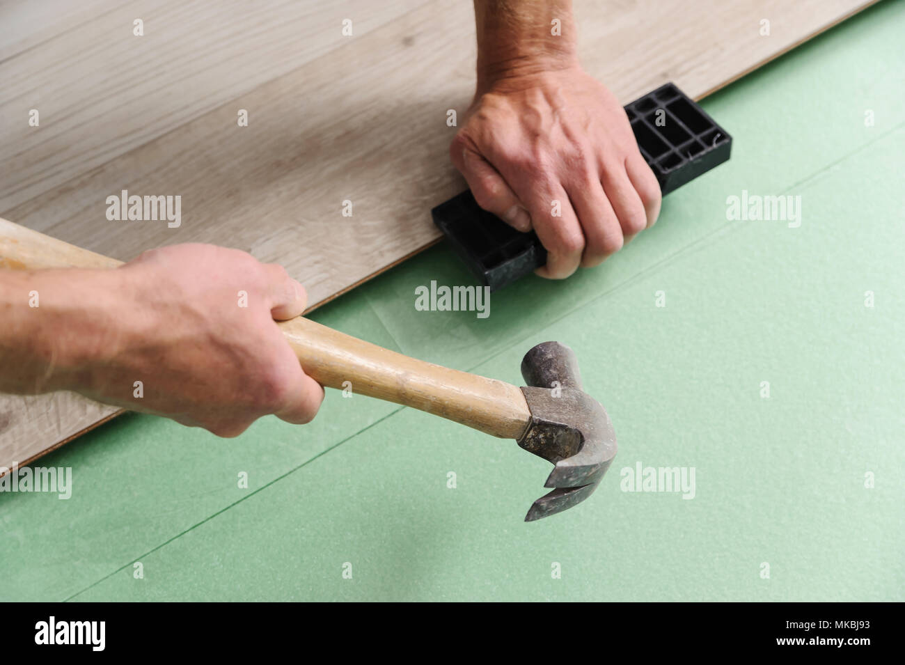 Installing laminate flooring. Worker lining boards to each other - Stock Image