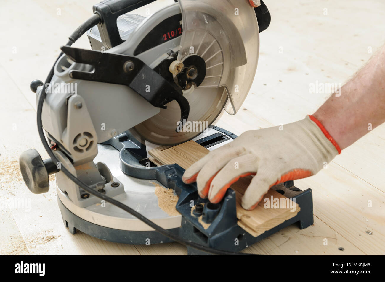 Worker cuts wooden floorboards using a circular saw. Stock Photo