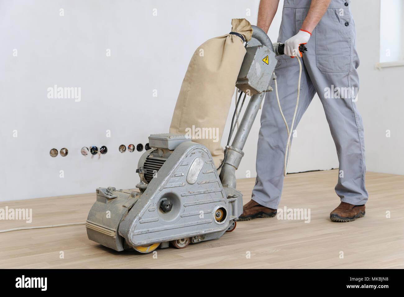 Worker polishing hardwood parquet floor with grinding machine. Stock Photo