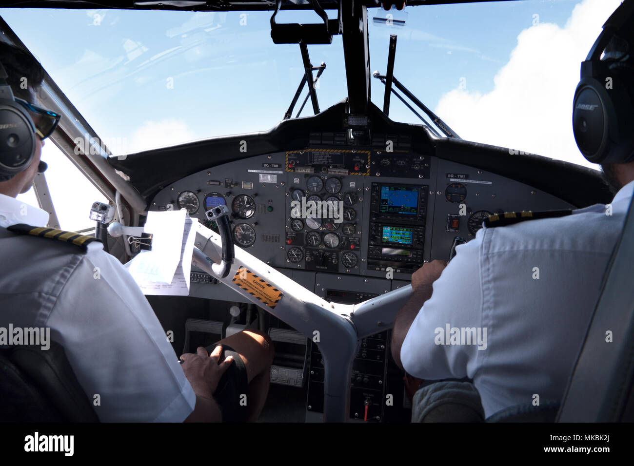 View of the cockpit of a small airplane flying in the sky. Team of pilots on plane, crew touching equipment and commands on dashboard - Stock Image