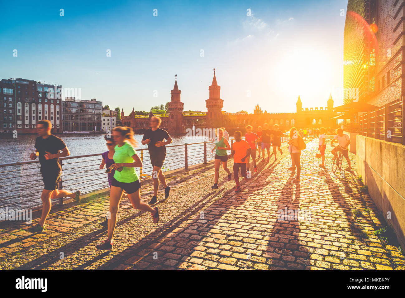 Group of female and male young runners jogging outside in golden evening light at sunset in summer with retro vintage filter effect - Stock Image