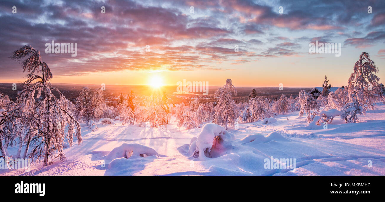 Panoramic view of beautiful winter wonderland scenery in scenic golden evening light at sunset with clouds in Scandinavia, northern Europe - Stock Image