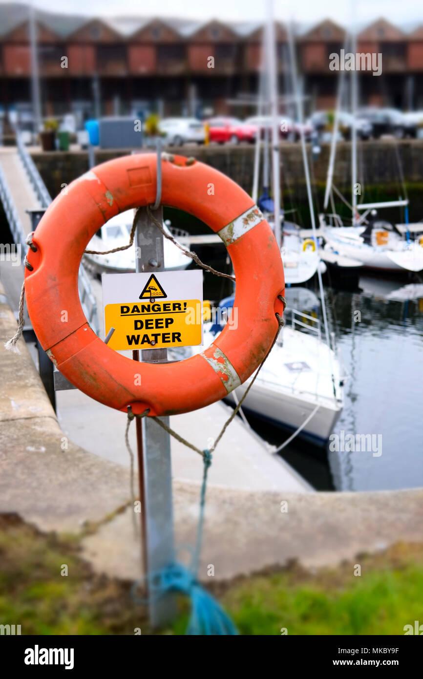 Water safety life deep risk danger red orange buoy ring save swimmer dock harbour harbor coastal sea marina Stock Photo