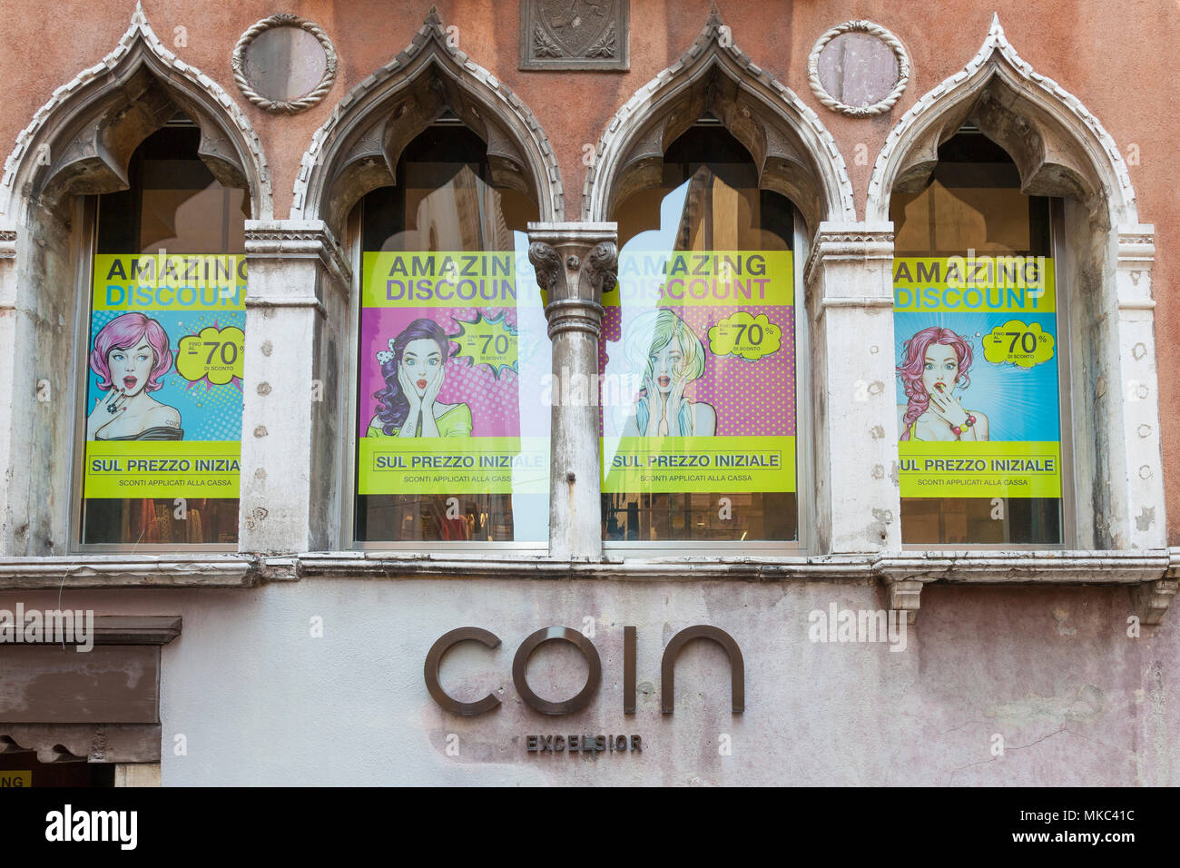 The sign on the historic Coin Excelsior Luxury Goods Store, Cannaregio, Venice, Veneto, Italy with Sale  posters in the windows. Closing down after a  - Stock Image