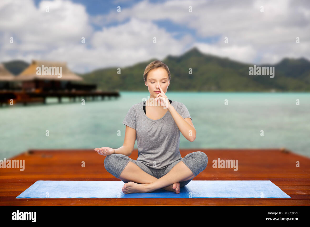 woman making yoga in and meditating lotus pose - Stock Image
