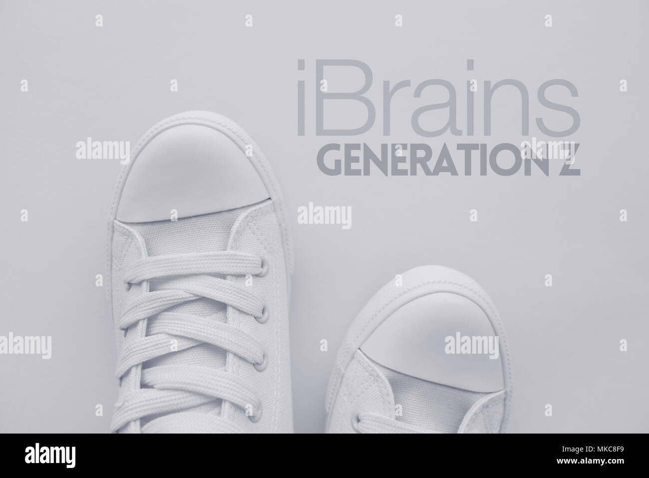 iBrains or Generation Z concept. Member of so called selfie generation in white casual canvas shoes standing over the title, top view - Stock Image
