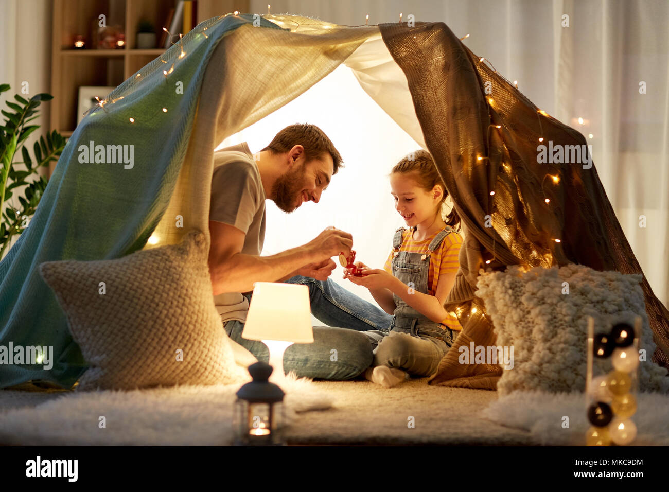 family playing tea party in kids tent at home - Stock Image