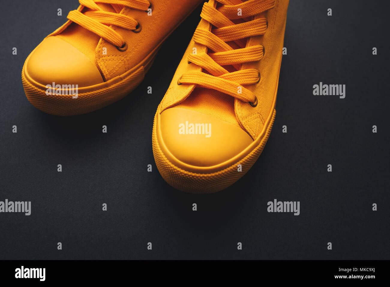 Stylish yellow sneakers on dark