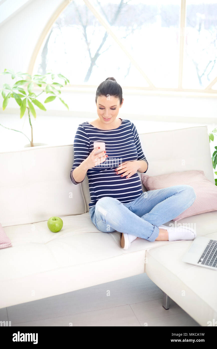 Happy pregnant woman using her mobile phone while sitting on sofa. - Stock Image