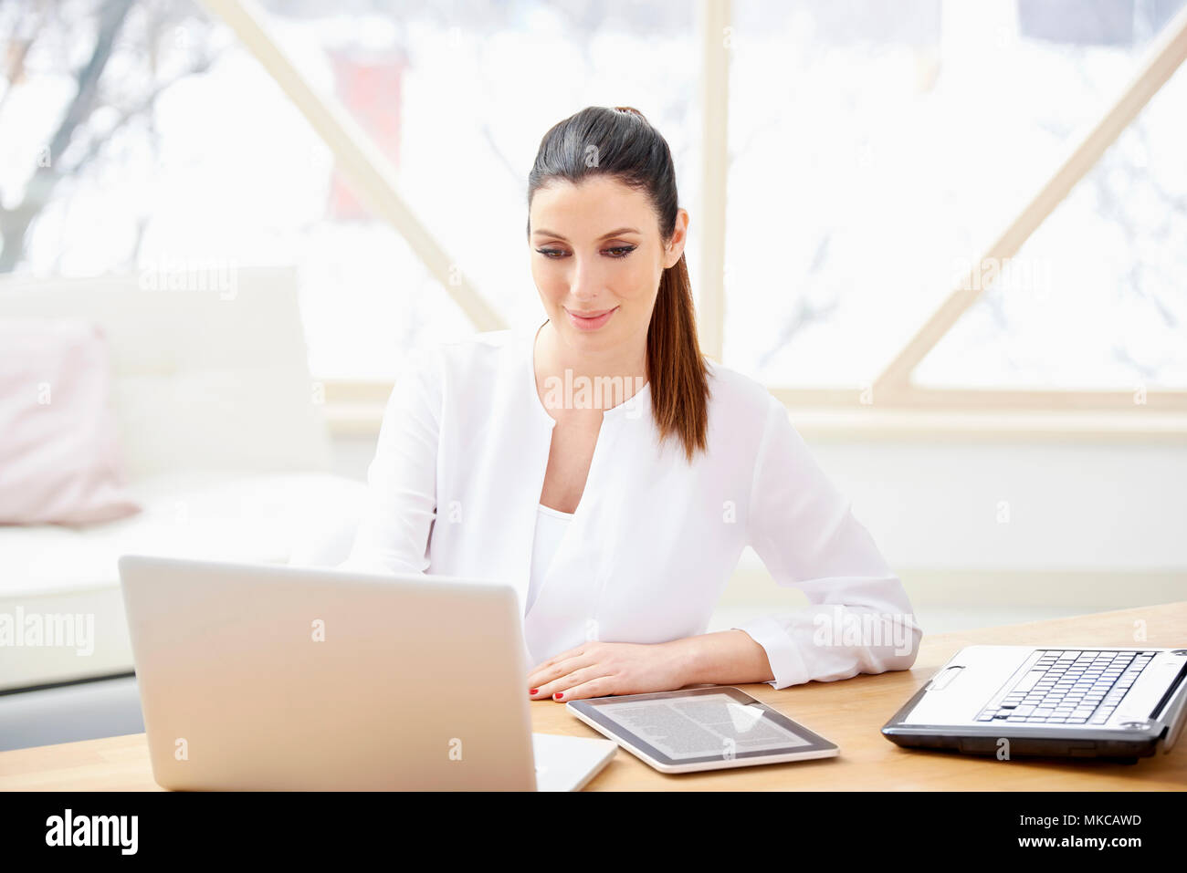 Beautiful young woman sitting at office desk behind computers and managing her business. Home office. - Stock Image