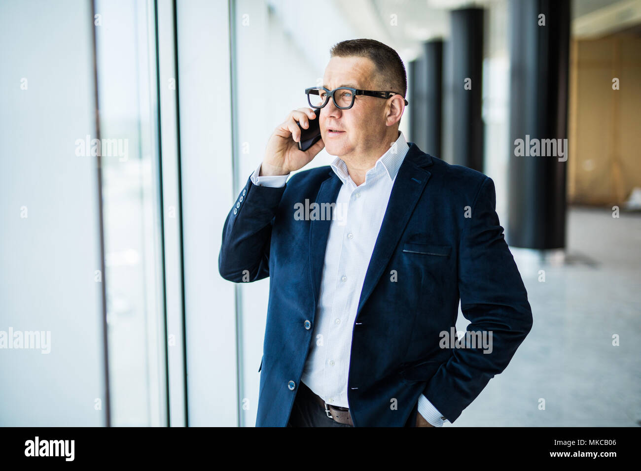 Smiling middle aged businessman using cellphone sitting in front of window overlooking cityscape - Stock Image