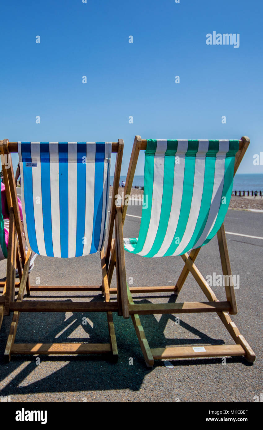Deckchairs on Littlehampton seafront promenade on a clear sunny day, West Sussex, UK - Stock Image