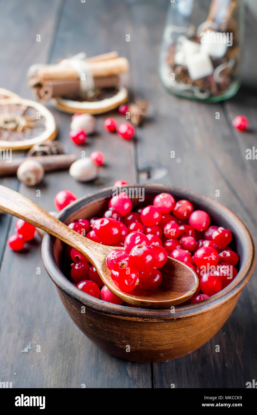 juicy raw cranberries in a ceramic plate, cinnamon stick, anise and dry orange on a dark old wooden table, ingridients for winter drink , copy space - Stock Image