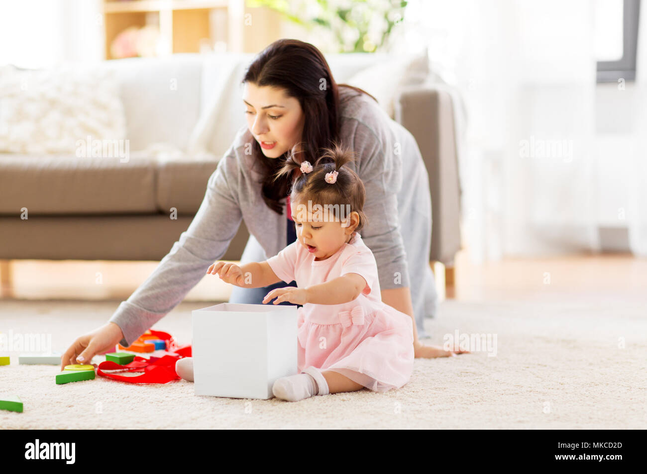 baby girl playing with toy or gift box at home - Stock Image