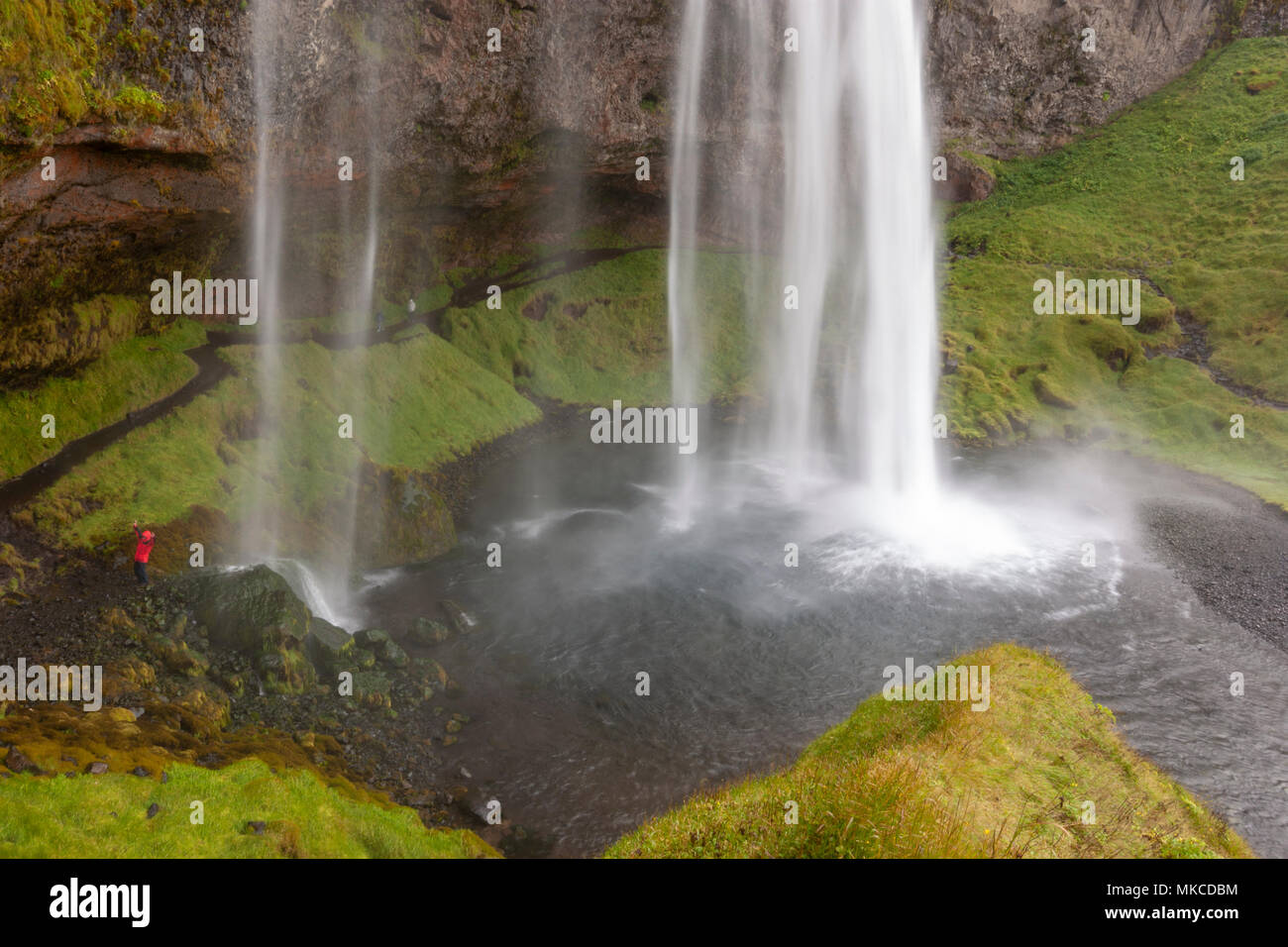 Tourist in front Seljalandsfoss waterfall cave, Iceland - Stock Image