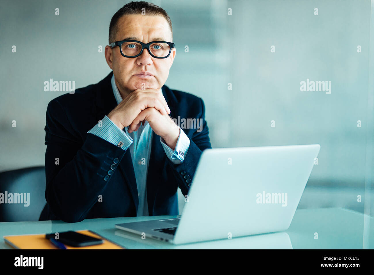 Businessman sitting working at a laptop computer in a large office - Stock Image