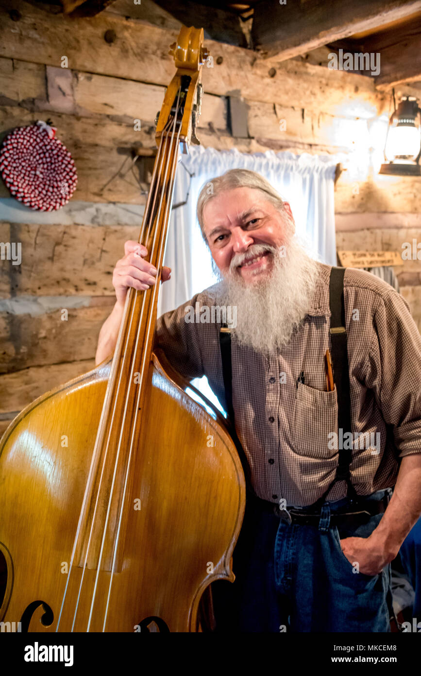 Portrait of a Silver Dollar City musician bass player smiling in Ozarks cabin with white beard, suspenders. Mountain music at Branson, Missouri, USA Stock Photo