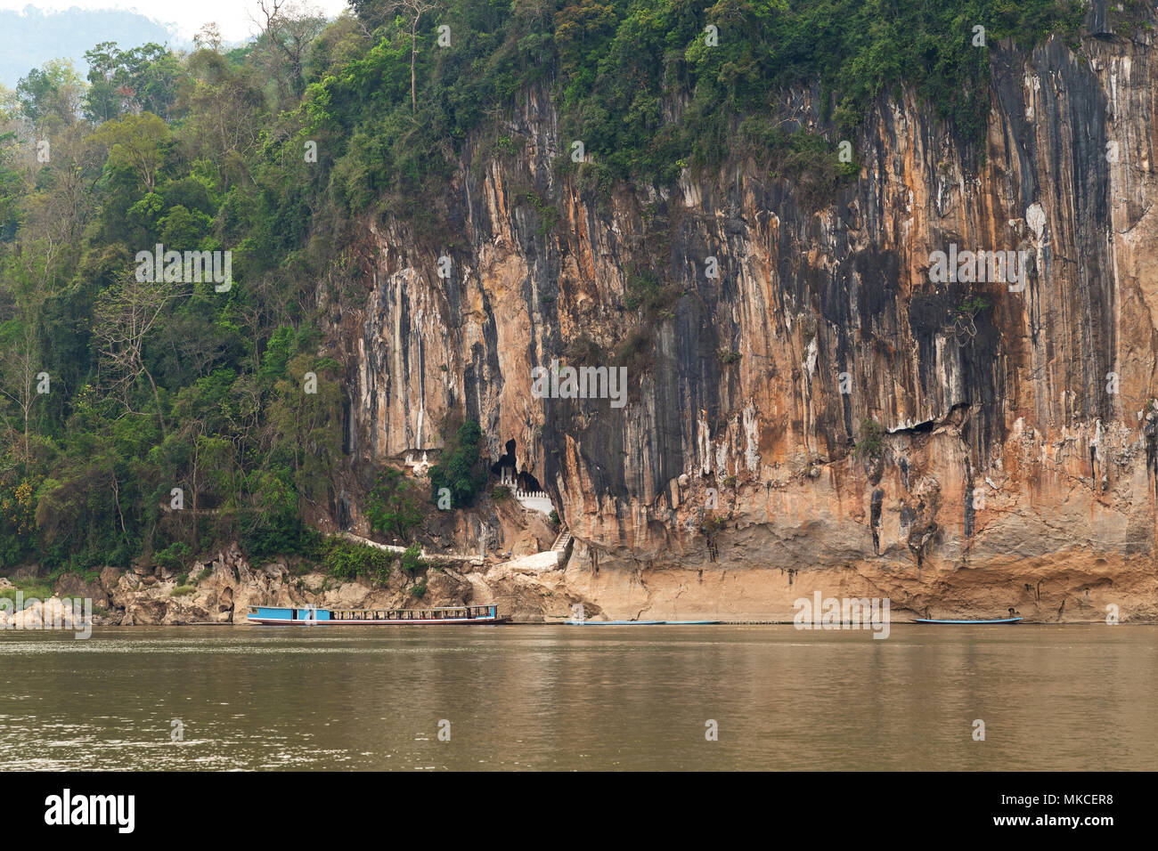 View of the Mekong River and limestone cliff where the famous Pak Ou Caves are set. They are located near Luang Prabang in Laos. - Stock Image