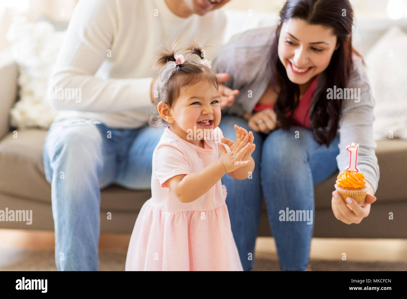 baby girl with parents at home birthday party - Stock Image
