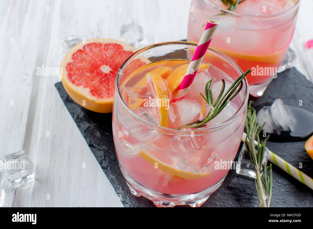 Cocktail with grapefruit slices and ice, ingredients for a drink on white wooden table, copy space Stock Photo