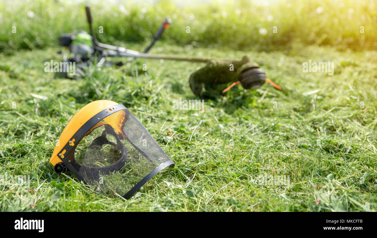 String trimmer and protective face mask on mown grass, growing grass on the background, banner 16x9 format - Stock Image
