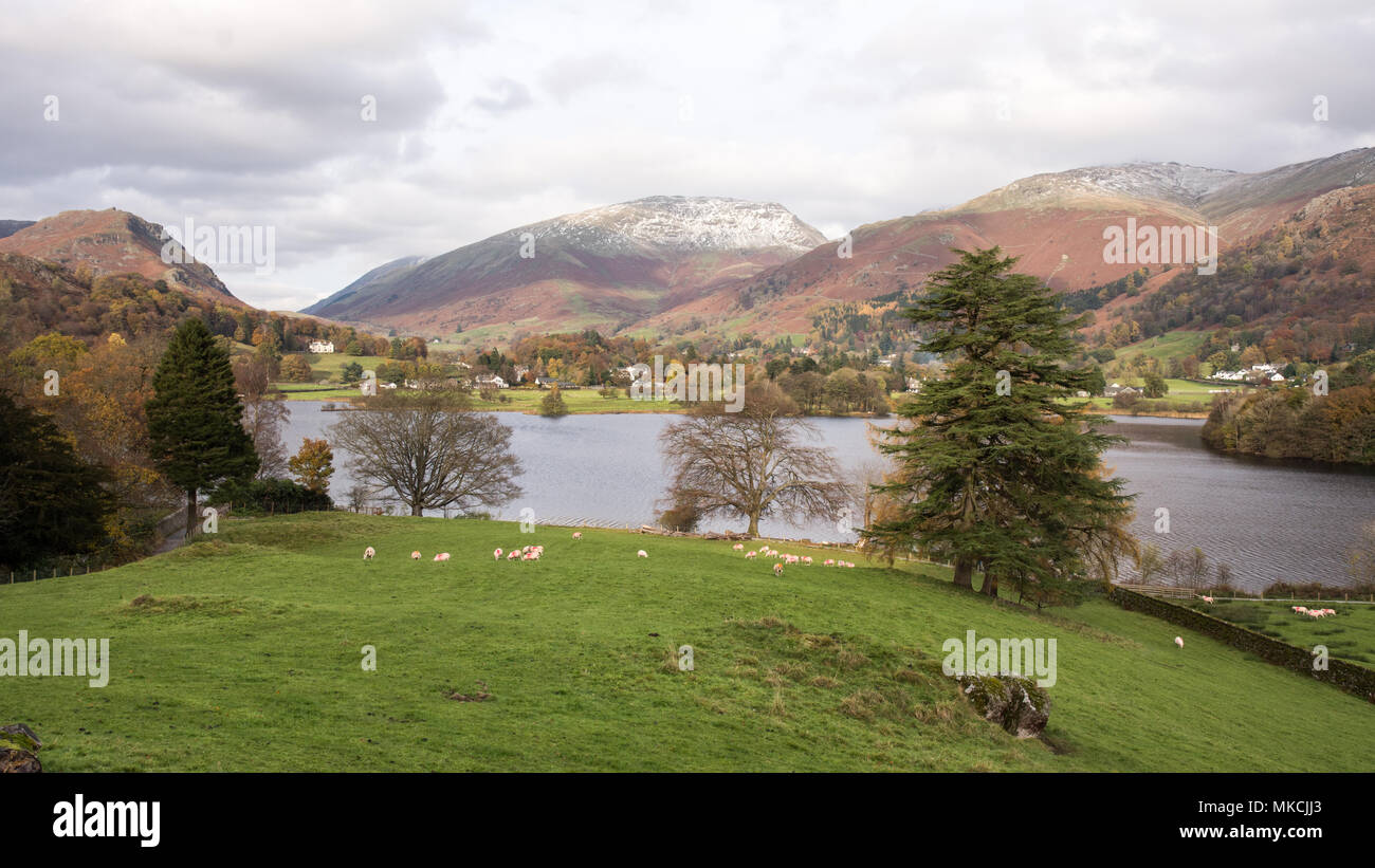 The snow-capped mountain of Seat Sandal rises behind Grasmere lake in England's Lake District National Park. - Stock Image