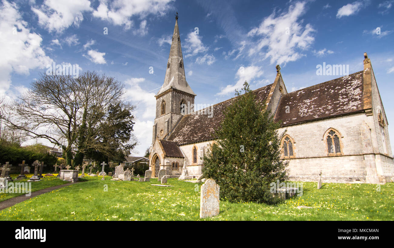 The traditional stone parish church with tower and spire in the village of Bradford Peverell near Dorchester in Dorset. - Stock Image