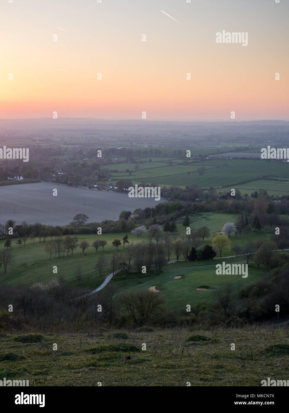 The sun sets over fields and villages in the agricultural landscape of the Aylesbury Vale, viewed from Combe Hill on the scarp of the Chiltern Hills. - Stock Image