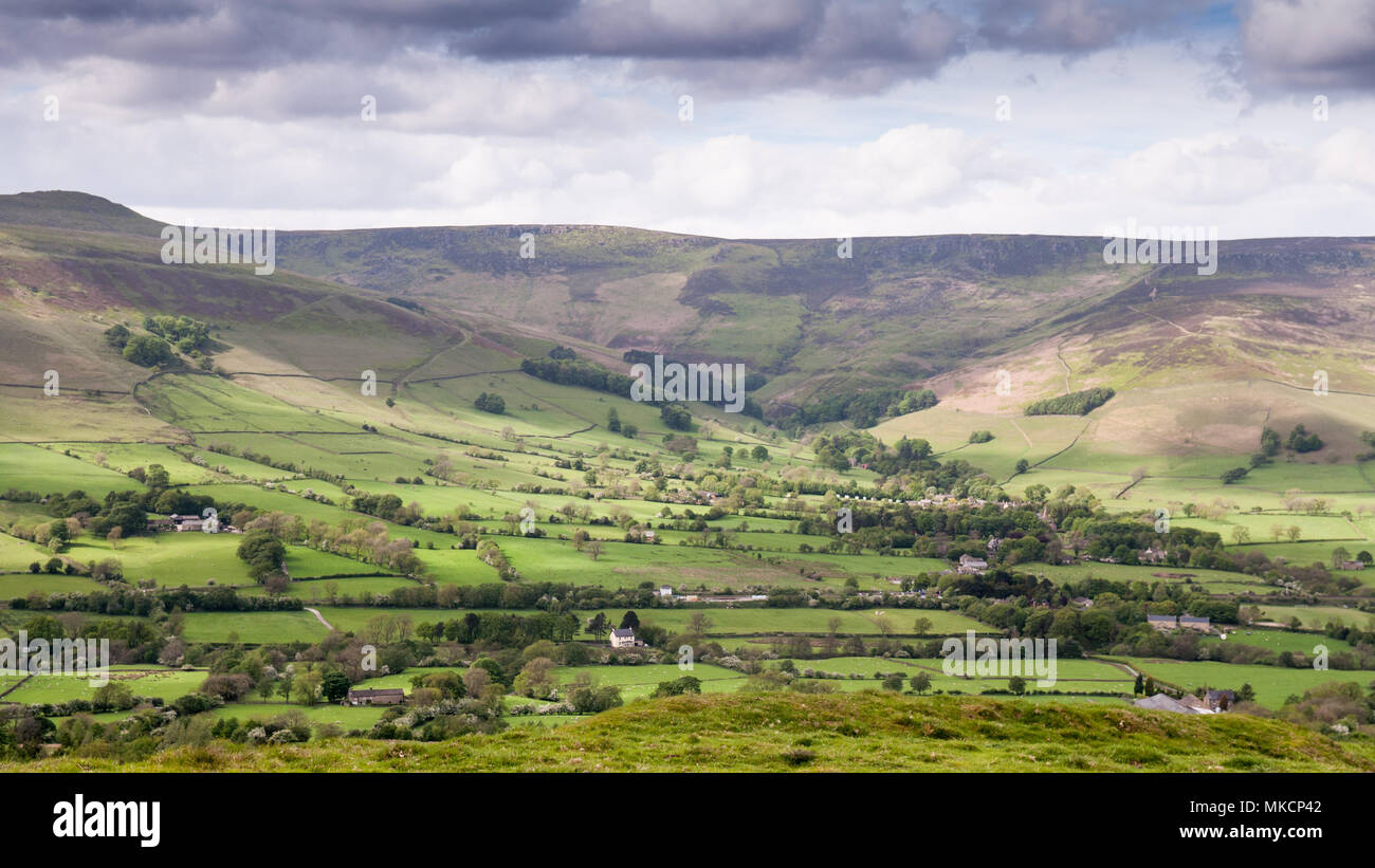 The moorland plateau of Kinder Scout rises above the lush pasture fields of Edale valley in Derbyshire, in England's Peak District National Park. - Stock Image