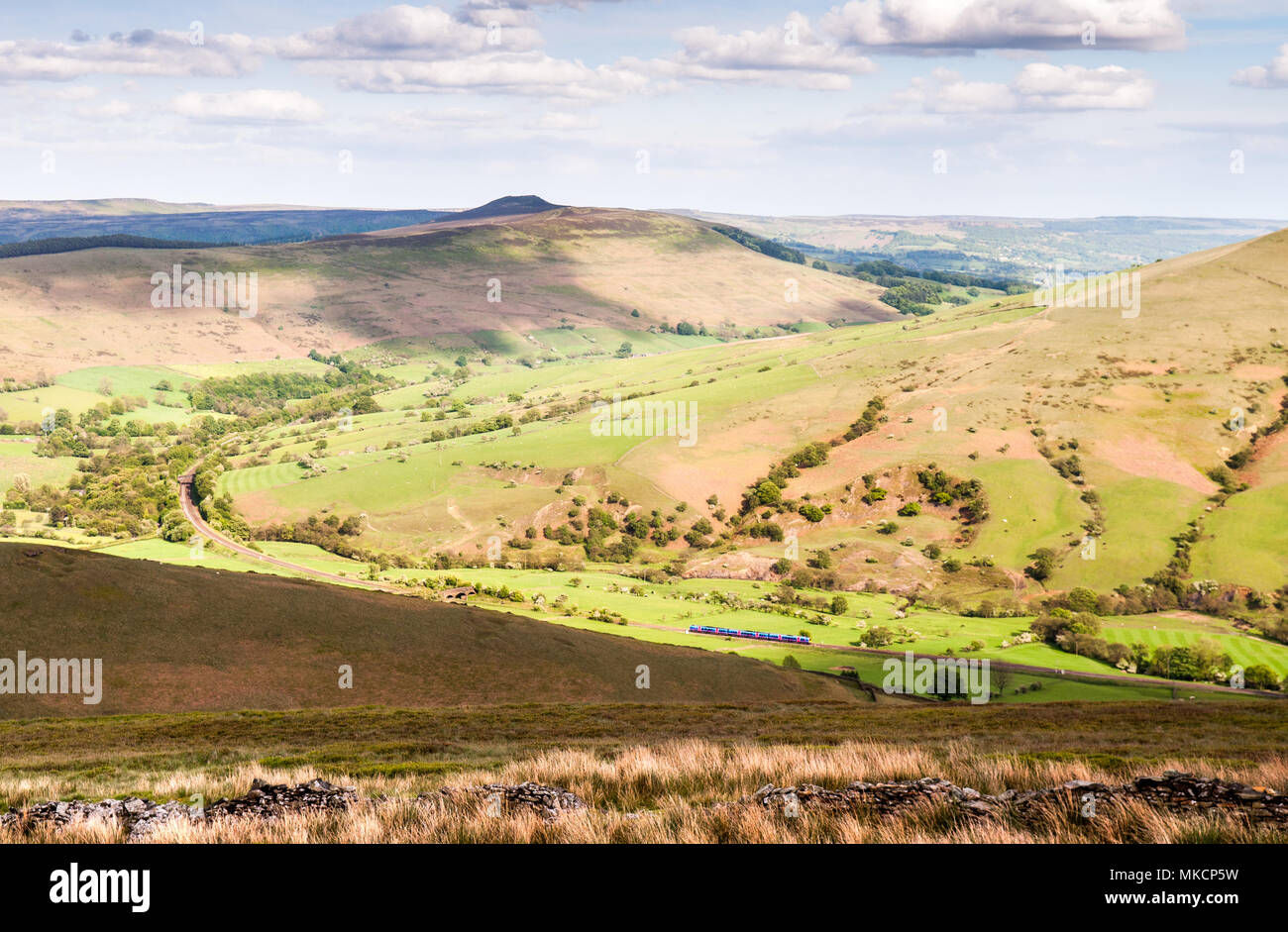 A TransPennine Express Class 185 passenger train travelling through Edale on the Hope Valley Line, seen from the moorland above. - Stock Image