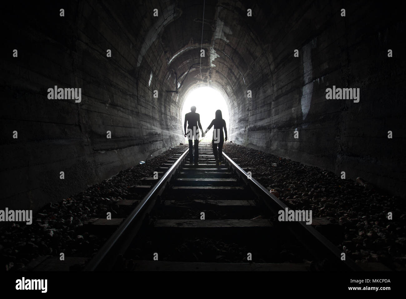 Couple walking hand in hand along the track through a railway tunnel towards the bright light at the other end, they appear as silhouettes against the - Stock Image