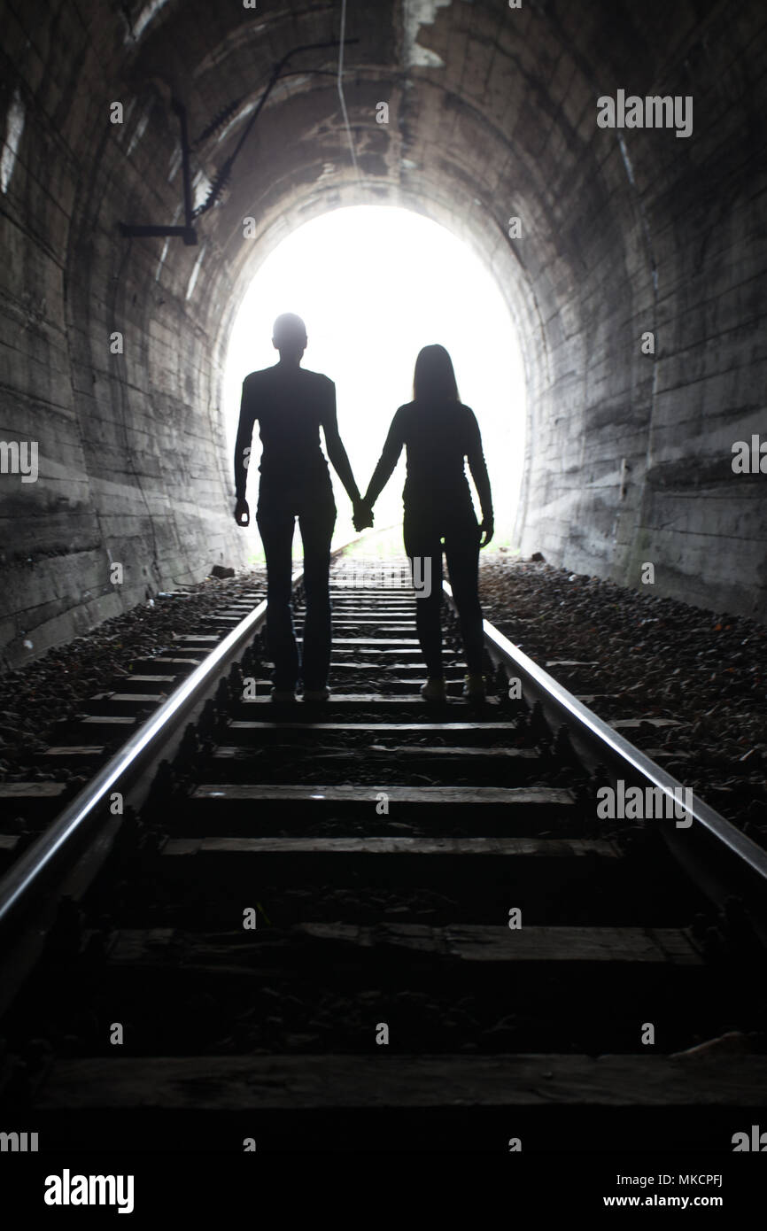 Couple walking hand in hand along the track through a railway tunnel towards the bright light at the other end, they appear as silhouettes against the Stock Photo