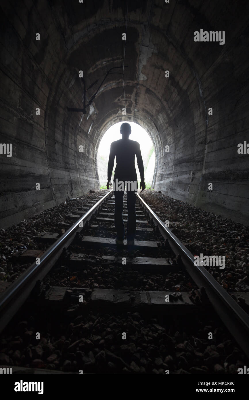 Man silhouetted in a tunnel standing in the center of the railway tracks looking towards the light at the end of the tunnel in a conceptual image - Stock Image