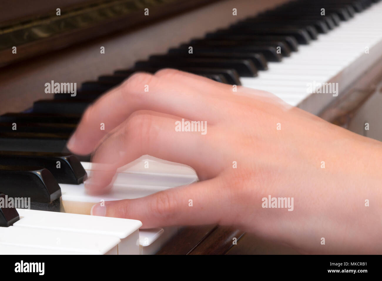 Close up of a woman's hand playing piano with motion blur - Stock Image