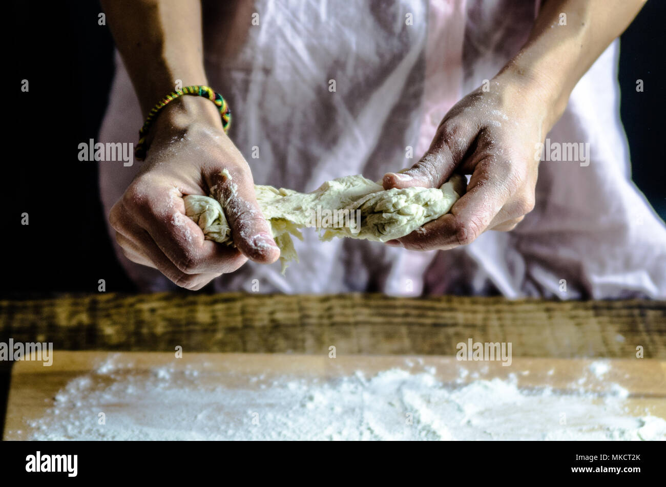 dough docked on the wooden board, traditional pretzel preparation, baker making bread dough in the bakery. hands played with flour and dough. - Stock Image