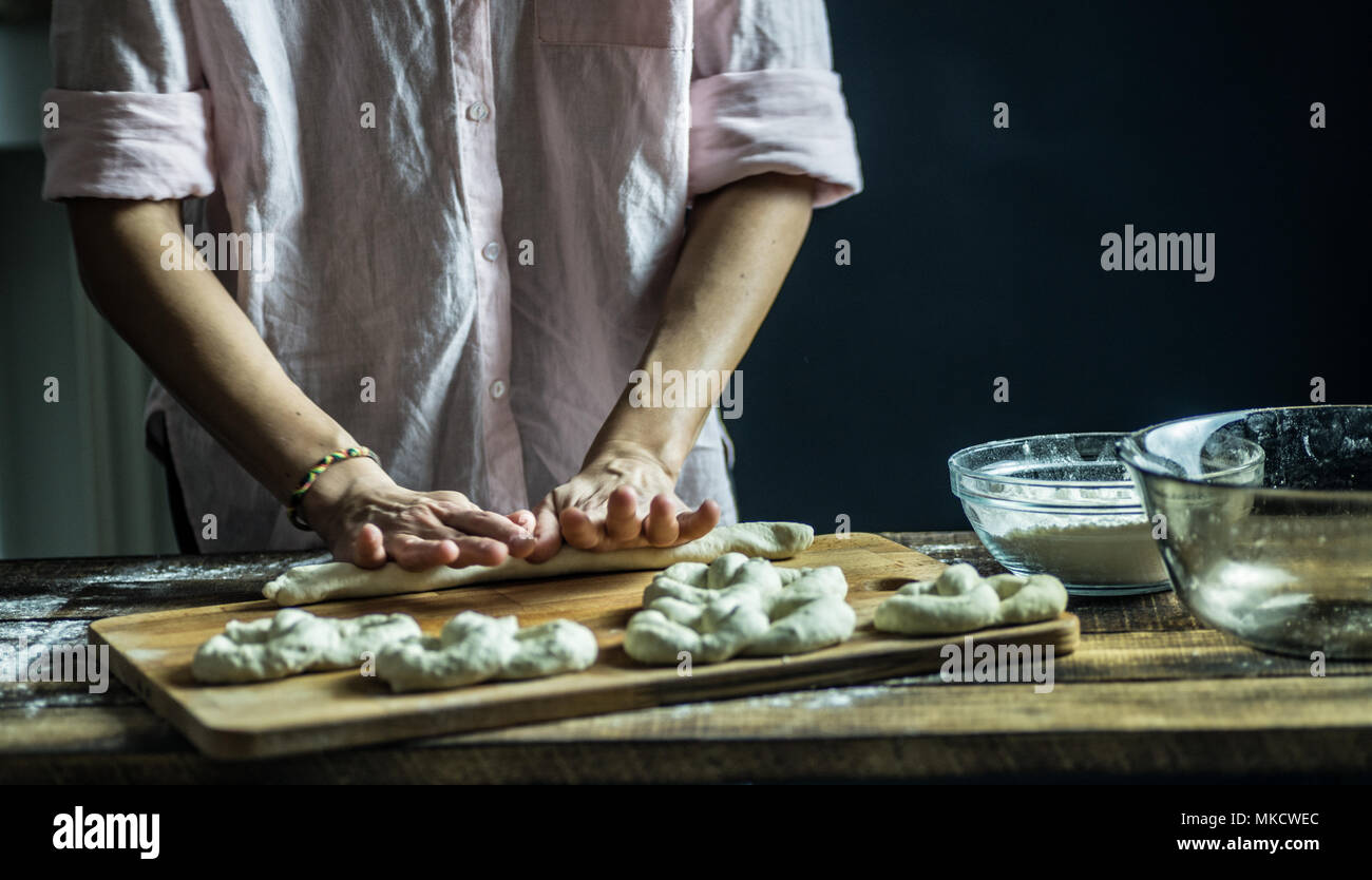 Dough dainted by the woman on the board - Stock Image