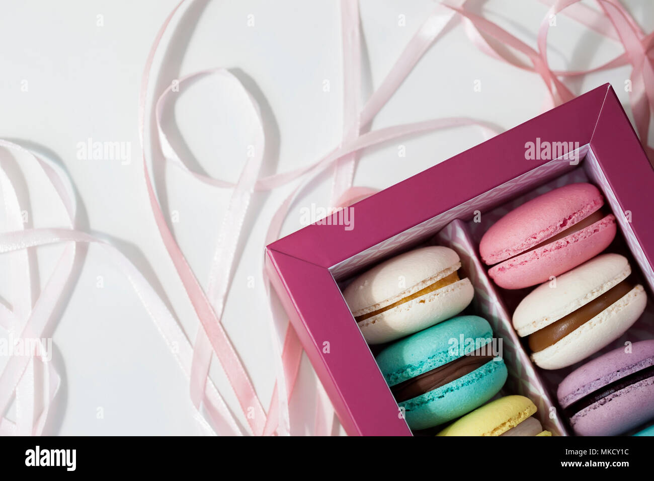 Box of macaroons of different colors with different tastes close-up on a light background for your text, top view - Stock Image