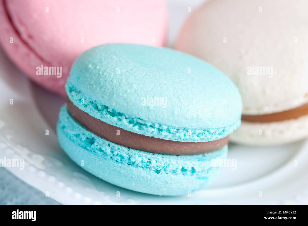 Three macaroons of different colors and different tastes in a white plate close-up - Stock Image