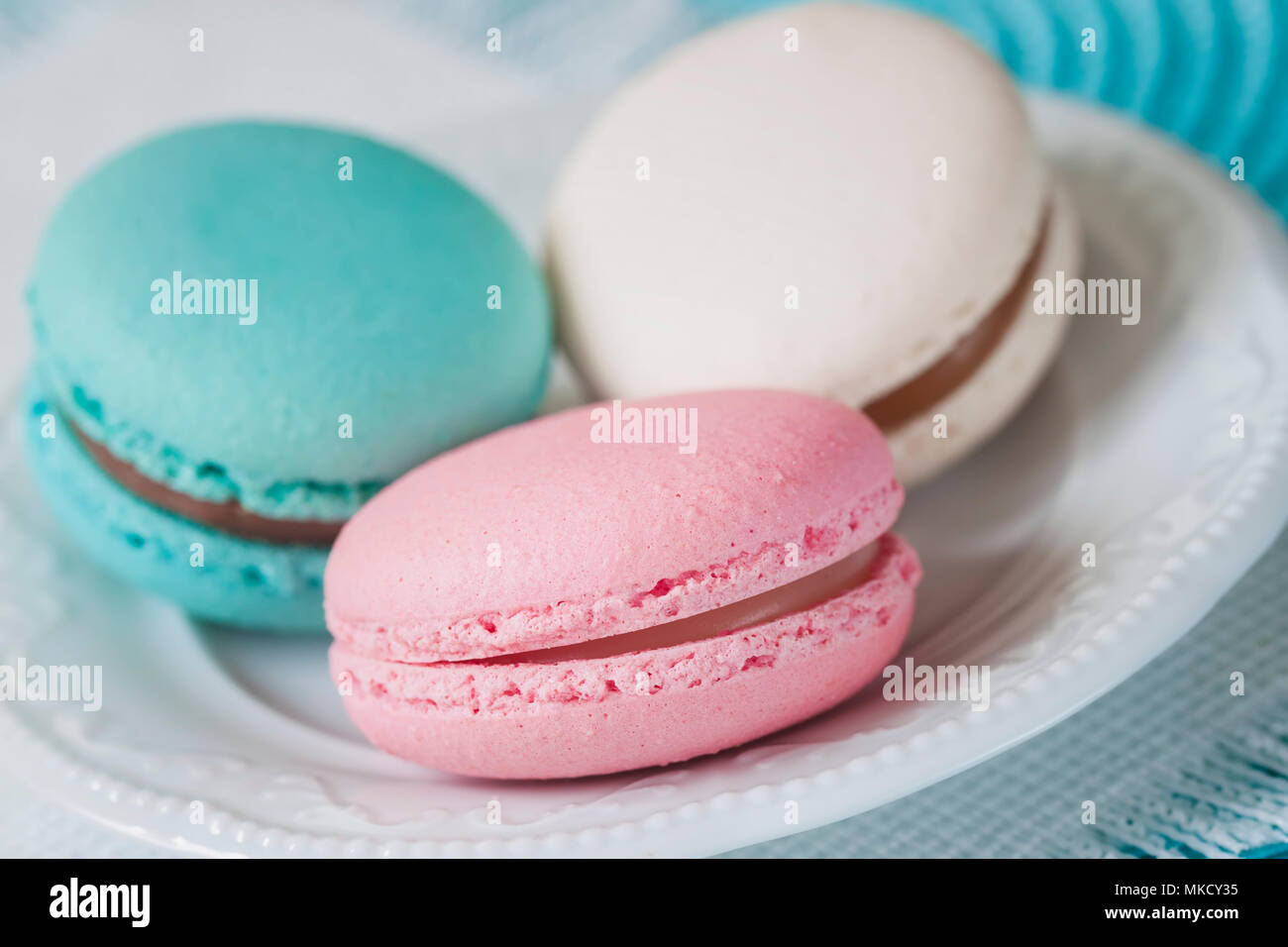 Three macaroons of different colors and different tastes in a white plate, top view. Romantic morning, gift for beloved. Breakfast on Valentin's, Mothers, Women's day. Tender background - Stock Image