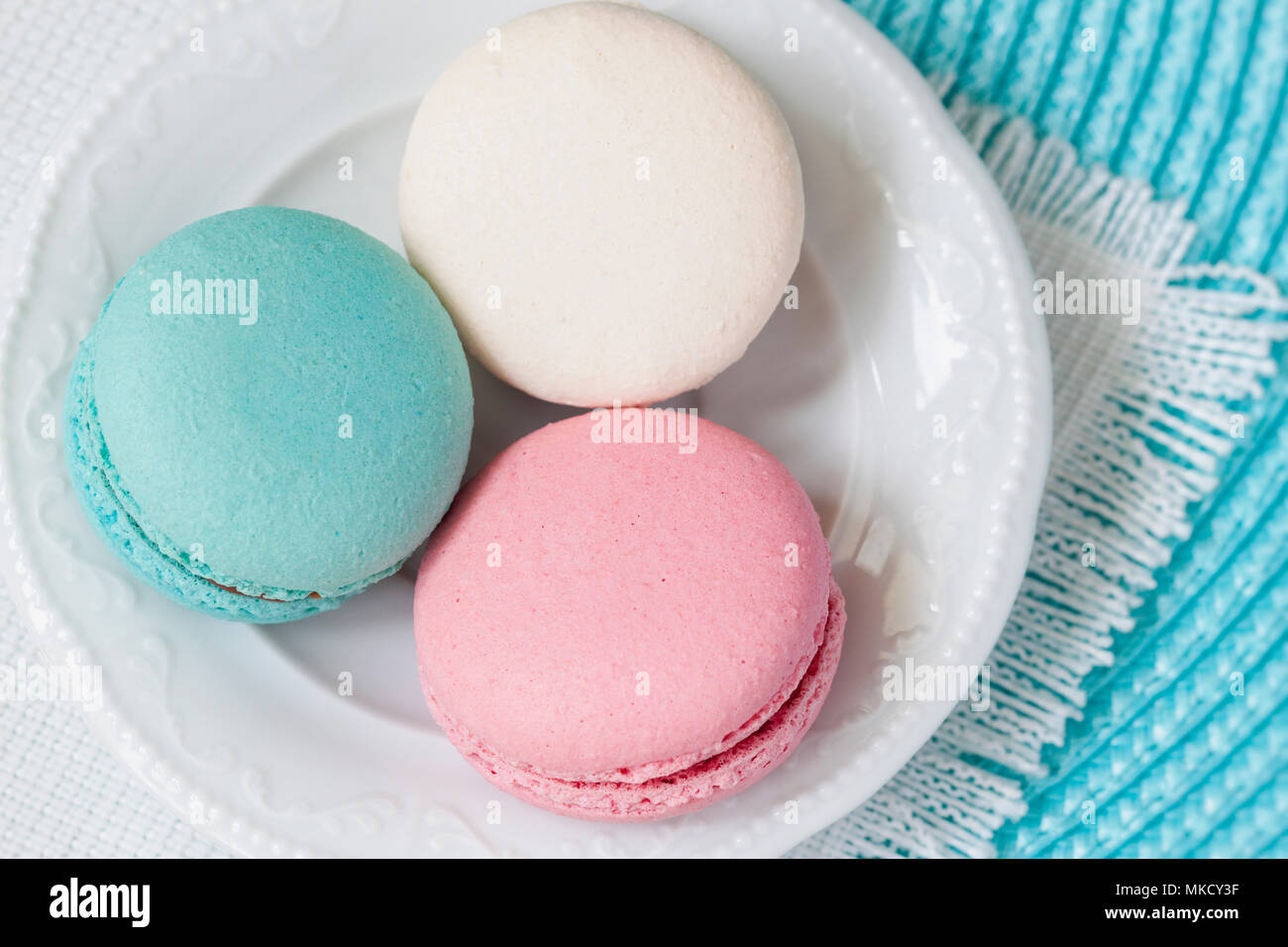 Three macaroons of different colors and different tastes in a white plate, top view. Romantic morning, gift for beloved. Breakfast on Valentin's, Mothers, Women's day - Stock Image