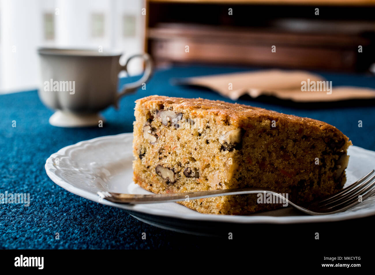 Carrot Cake with walnuts and cinnamon on blue surface. Stock Photo