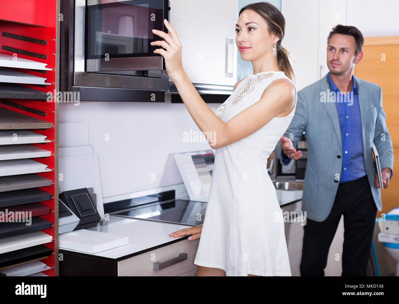 Successful positive seller and glad woman at kitchen furniture